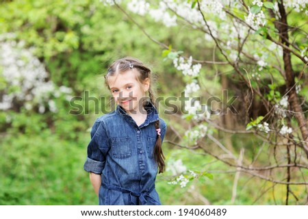 Outdoor portrait of a cute child girl near blooming apple tree - stock photo