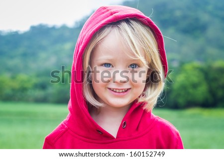 Outdoor portrait of a cute child in a red hooded jumper with a green background - stock photo