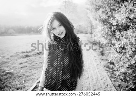 Outdoor portrait of a cute kid girl with long brunette hair on sunset, playing in the park in black and white editing - stock photo