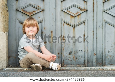 Outdoor portrait of a cute little blond boy of 4 years old, wearing grey t-shirt, beige trousers and white sandals - stock photo