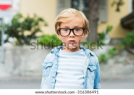 Outdoor portrait of a cute little boy in glasses. - stock photo