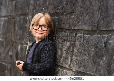 Outdoor portrait of a cute little boy in glasses - stock photo