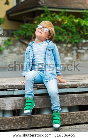 Outdoor portrait of a cute little boy in glasses, wearing denim clothes and green shoes - stock photo