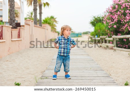 Outdoor portrait of a cute little boy, wearing plaid blue shirt - stock photo