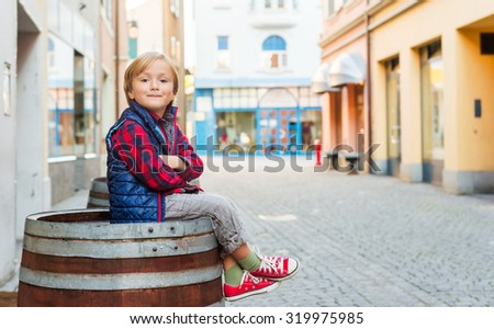 Outdoor portrait of a cute little boy, wearing red shirt and blue jacket - stock photo