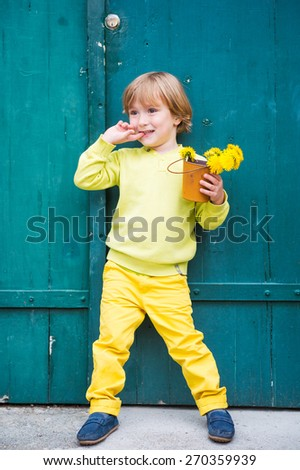 Outdoor portrait of a cute little boy, wearing yellow pullover and trousers and blue moccasins, standing by the green wooden door, holding bucket with flowers dandelions - stock photo
