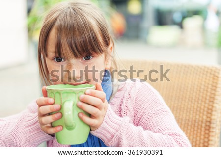 Outdoor portrait of a cute little girl drinking hot chocolate in a cafe - stock photo