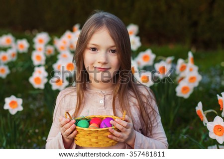 Outdoor portrait of a cute little girl in a spring garden, holding small basket with colorful easter eggs - stock photo