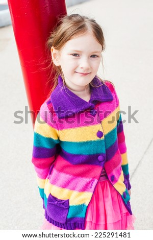 Outdoor portrait of a cute little girl in a street on a fresh day