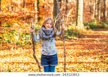 Outdoor portrait of a cute little girl in autumn forest - stock photo