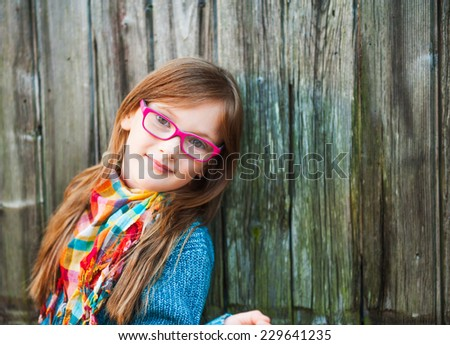 Outdoor portrait of a cute little girl in glasses - stock photo
