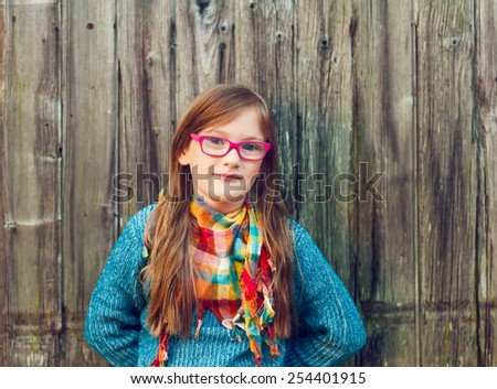 Outdoor portrait of a cute little girl in glasses, toned image - stock photo