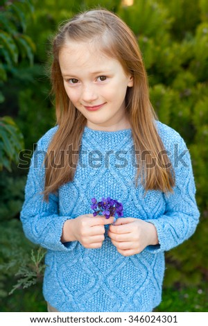 Outdoor portrait of a cute little girl of 7 years old, wearing blue pullover, holding first spring flowers violets