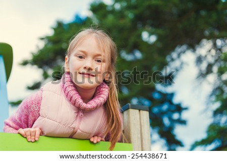 Outdoor portrait of a cute little girl on playground - stock photo
