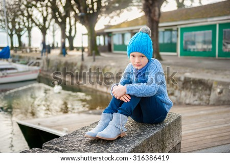 Outdoor portrait of a cute little girl resting by the lake in a small port, wearing warm blue pullover, hat, boots - stock photo