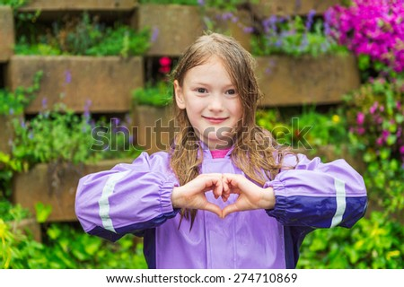 Outdoor portrait of a cute little girl under the rain, wearing purple rain coat, making heart sign with her hands