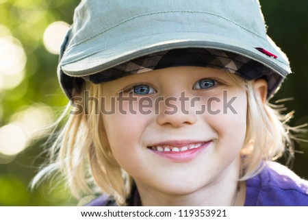 Outdoor portrait of a cute smiling boy wearing a hat