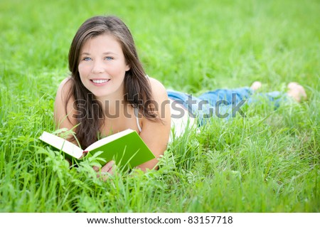 Outdoor portrait of a cute teen reading a book while lying in green grass in summer