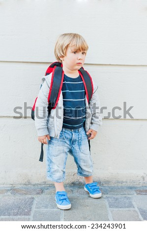 Outdoor portrait of a cute toddler boy, going to kindergarten with backpack - stock photo