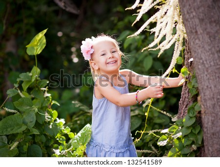 Outdoor portrait of a cute toddler girl holding to a tree and smiling into camera - stock photo
