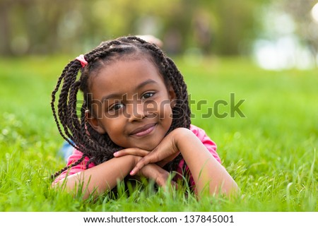 Outdoor portrait of a cute young black girl  lying down on the grass and smiling - African people - stock photo