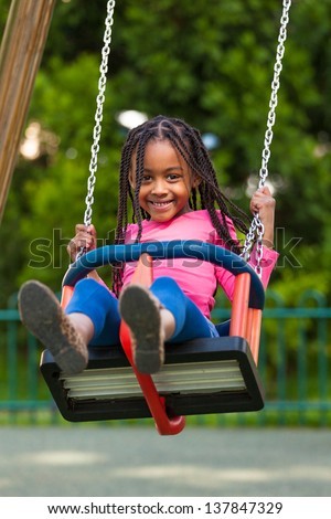 Outdoor  portrait of a cute young black girl playing with a swing - African people