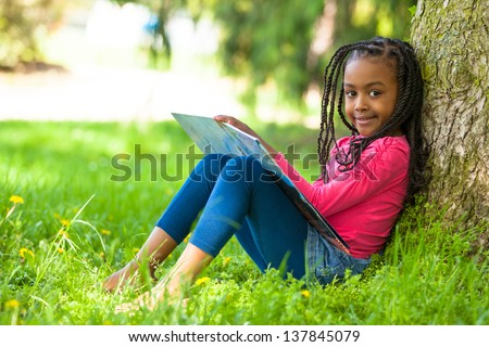Outdoor portrait of a cute young black little  girl reading a book - African people - stock photo