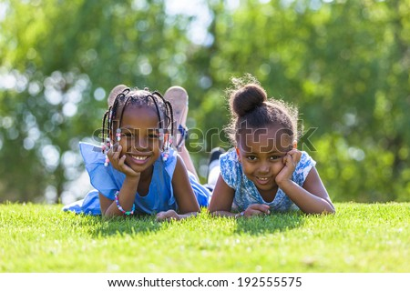 Outdoor portrait of a cute young black sisters  lying down on the grass and smiling - African people - stock photo