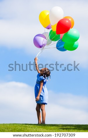 Outdoor portrait of a cute young  little black girl playing with balloons - African people - stock photo