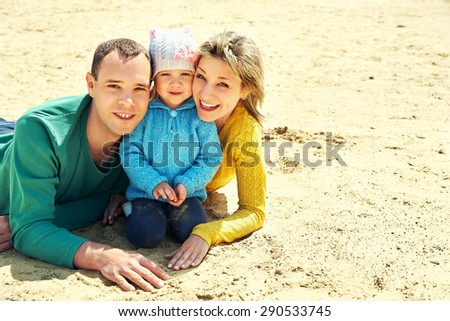 outdoor portrait of a family. young parents with a baby for a walk in the summer. Mom, dad and child - stock photo