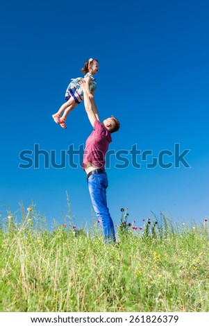 Outdoor portrait of a father who throws daughter on hands against the sky