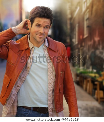 Outdoor portrait of a good looking young man walking outdoors - stock photo