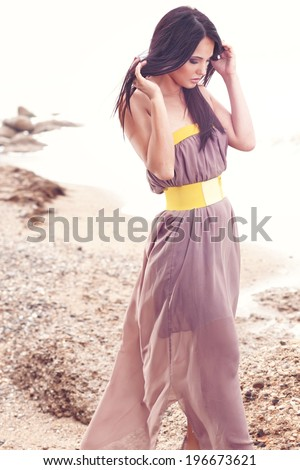 Outdoor portrait of a gorgeous fashion model dressed in maxi chiffon dress posing at the beach - stock photo