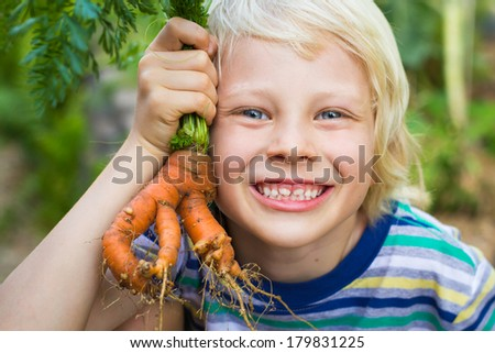 Outdoor portrait of a happy child showing an unusual organic homegrown carrot from his garden - stock photo