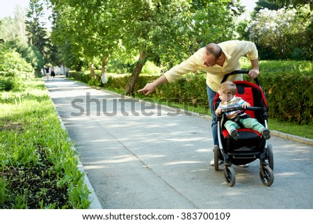 outdoor portrait of a happy father and son. baby sitting in stroller and dad walking in summer park - stock photo