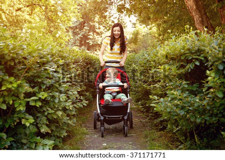 outdoor portrait of a happy mother and son. baby sitting in stroller and mom walking in the summer park - stock photo