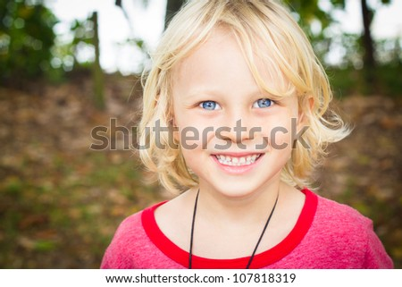 Outdoor portrait of a happy young boy - stock photo