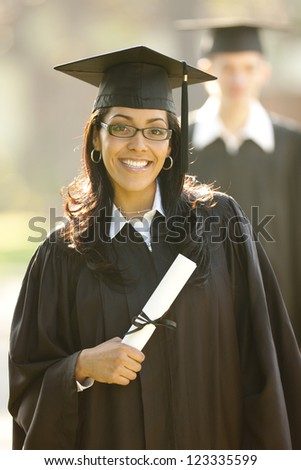 Outdoor portrait of a Hispanic female graduate wearing a graduation cap and gown holding her diploma - stock photo