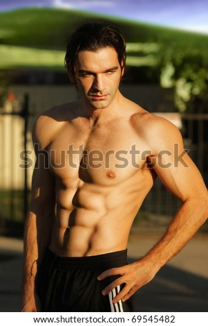 Outdoor portrait of a hunky fit male model shirtless - stock photo