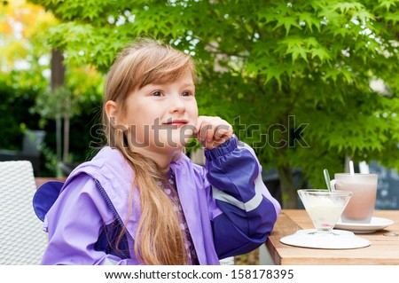 Outdoor portrait of a preschooler girl wearing rainy coat, sitting in cafe with ice cream and hot chocolate on a table - stock photo