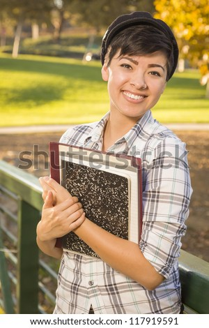 Outdoor Portrait of a Pretty Mixed Race Female Student Holding Books on a Sunny Afternoon. - stock photo