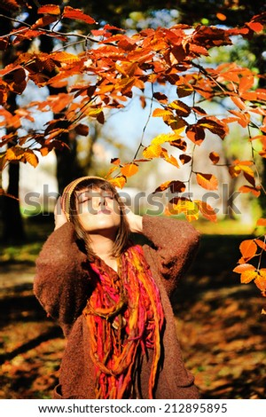 Outdoor portrait of a pretty young brunette woman relaxing in autumn park.  - stock photo
