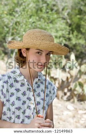 Outdoor portrait of a ranch girl in a straw hat, wearing a vintage flower print dress