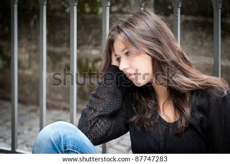Outdoor portrait of a sad teenage girl looking thoughtful about troubles - stock photo