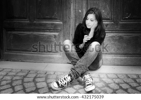 Outdoor portrait of a sad teenage girl looking thoughtful about troubles, black and white photo - stock photo