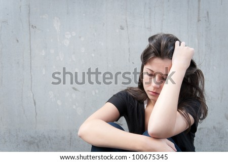 Outdoor portrait of a sad teenage girl looking thoughtful about troubles in front of a gray wall - stock photo