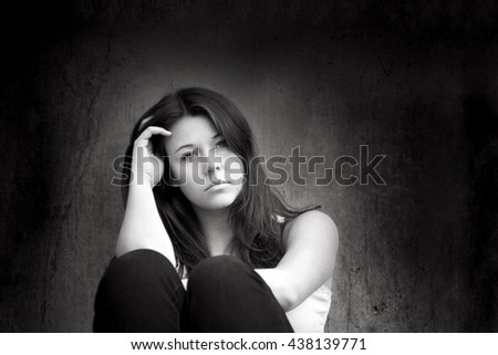 Outdoor portrait of a sad teenage girl looking thoughtful about troubles in front of a gray wall, black and white photo - stock photo