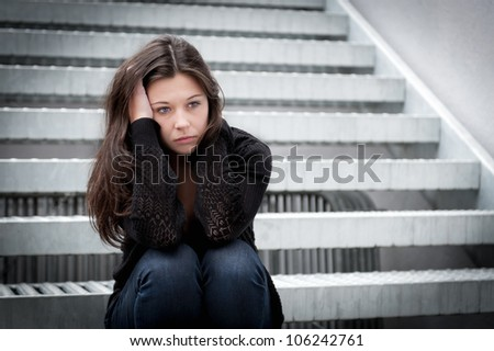 Outdoor portrait of a sad teenage girl looking thoughtful about troubles in front of a stairway - stock photo