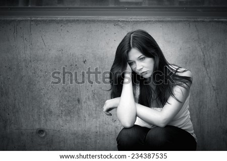 Outdoor portrait of a sad teenage girl looking thoughtful about troubles, monochrome photo - stock photo
