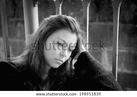 Outdoor portrait of a sad young woman looking thoughtful about troubles, monochrome - stock photo